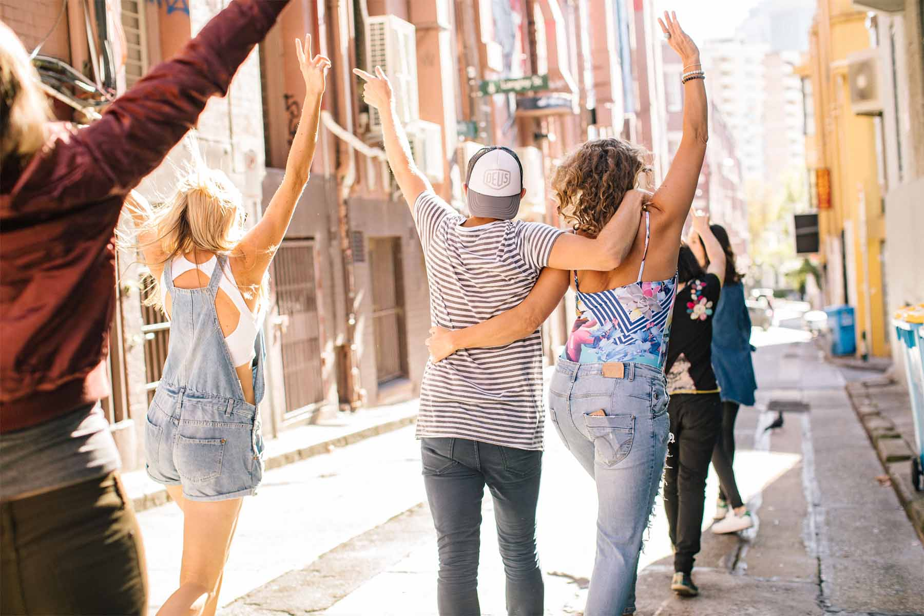 A Group of people are happilly skipping down a backstreet in Sydney for a social media photo shoot
