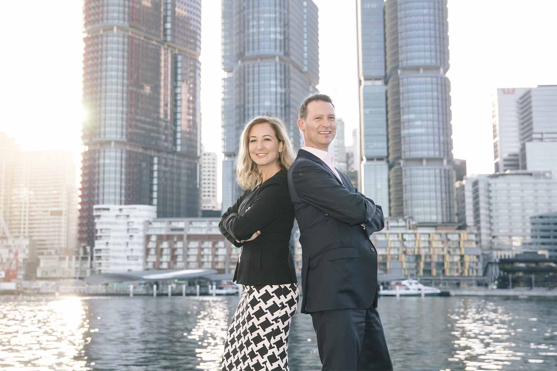 The 2 Directors of Oaktree talent stand back to back at sunrise with the International Towers of Barangaroo behind them