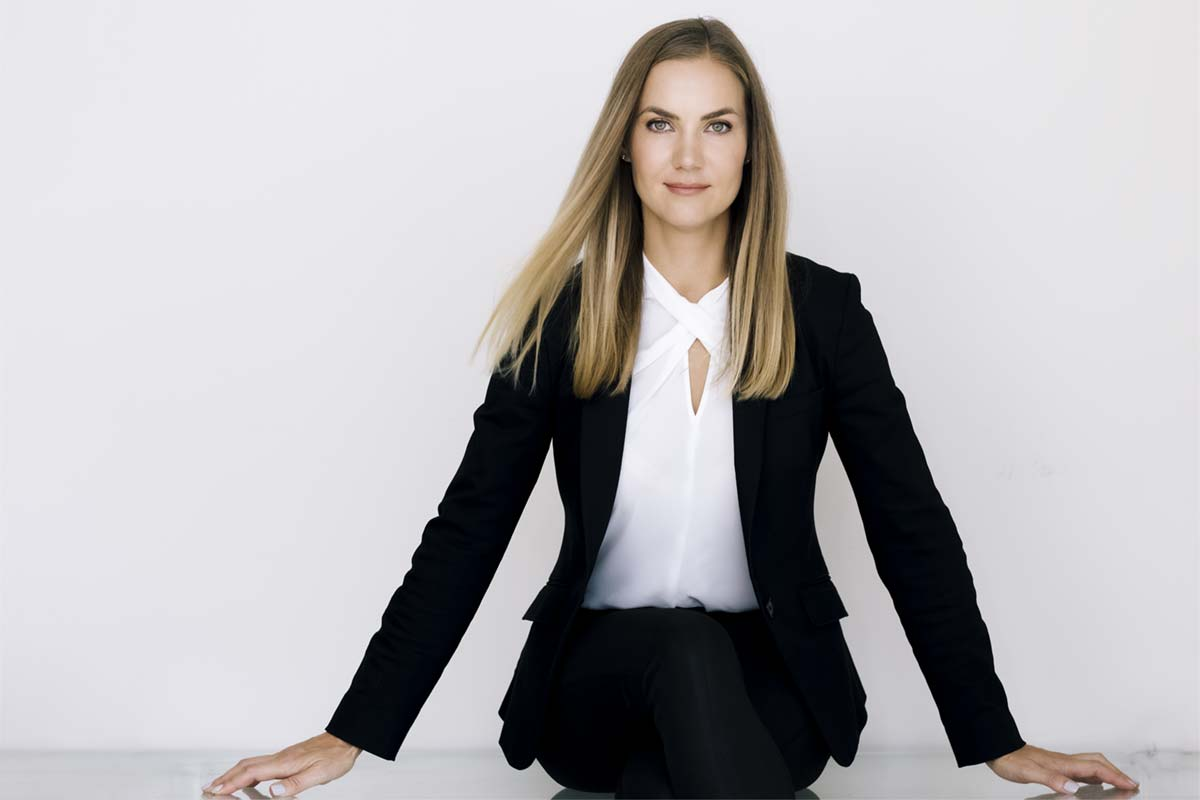 Wearing a business suit, Klaudia sits on a table for her portrait