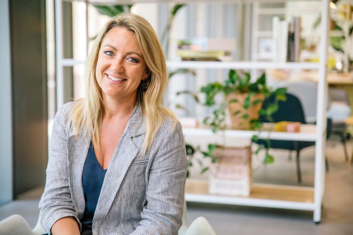 Dayna smiling in a bright office environment for her team page portrait