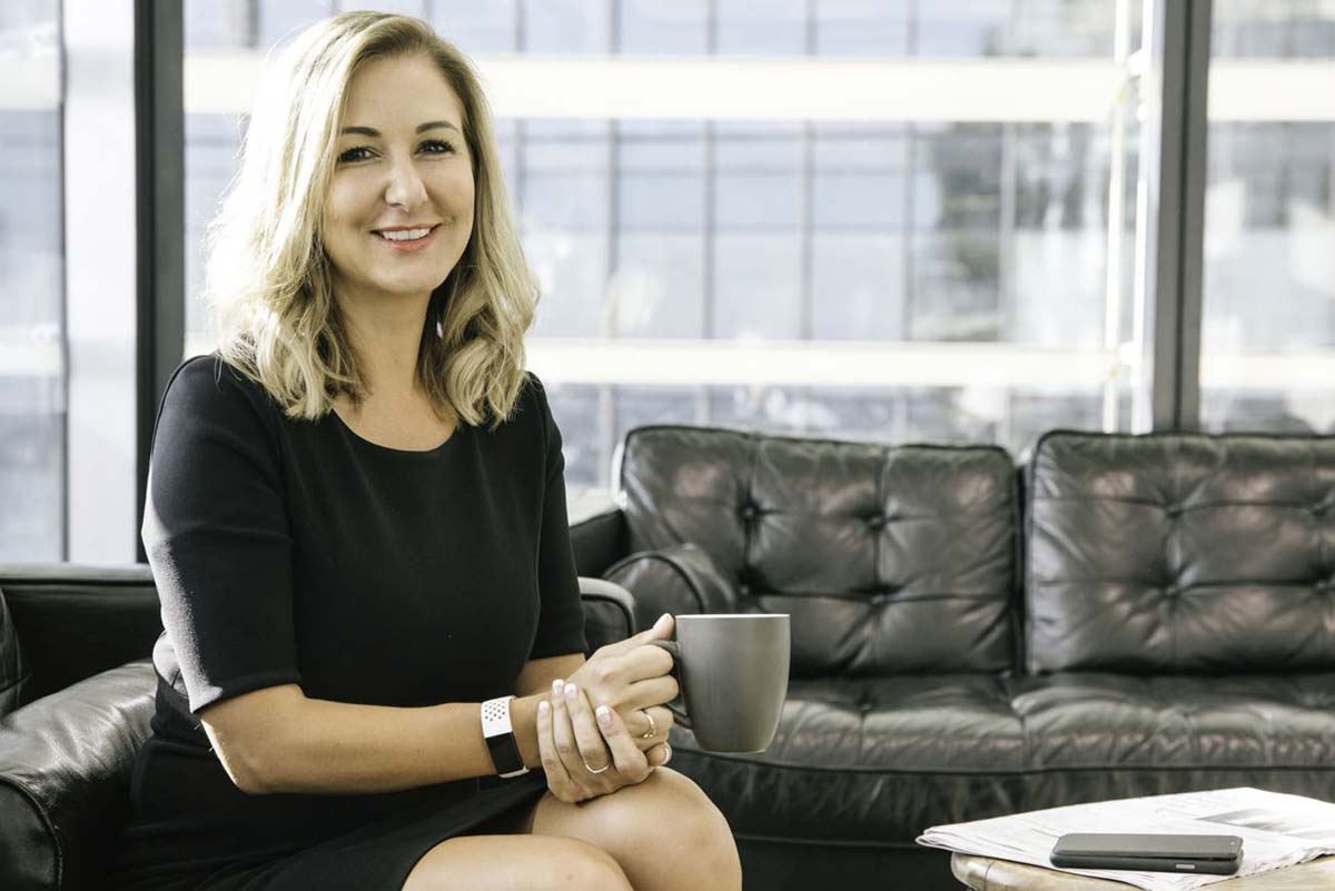 anika sits in barangaroo towers reading the paper and having a coffee on her website team page