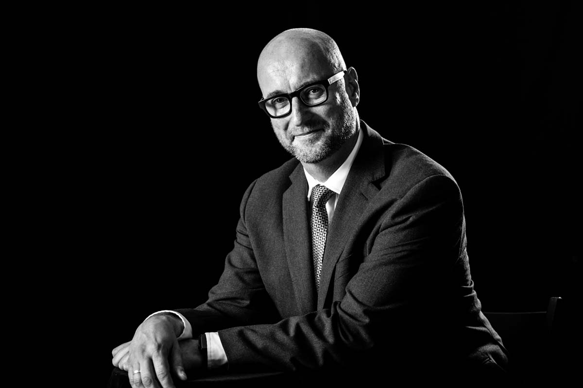 CEO looks natural and confident in corporate headshot with black background