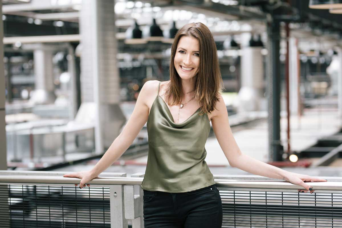 Drieli smiling wearing a green top in an industrial looking location for her personal brand shoot